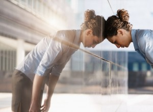 mid adult italian business woman banging her head against a wall outside office building. Square shape, copy space